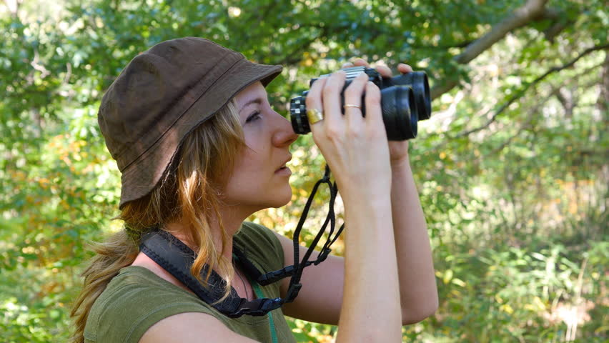 Female birdwatcher brings binoculars up to look at something.