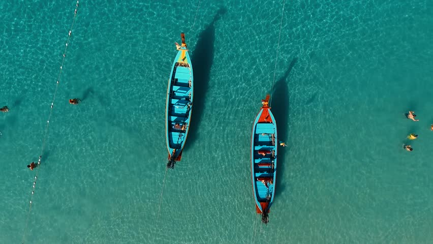 Aerial: Two long tail boats on the beach.
