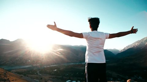young Asian male reaching to the top of the mountain area, standing on top of a mountain, hands raised, awareness of success, slow motion