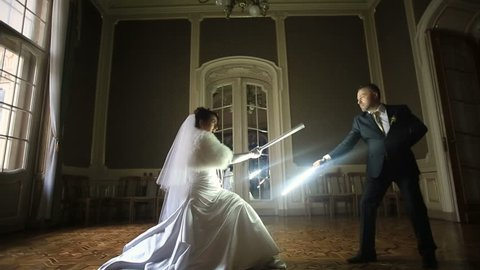 Funny bride and groom playing a Jedi with lightsabers