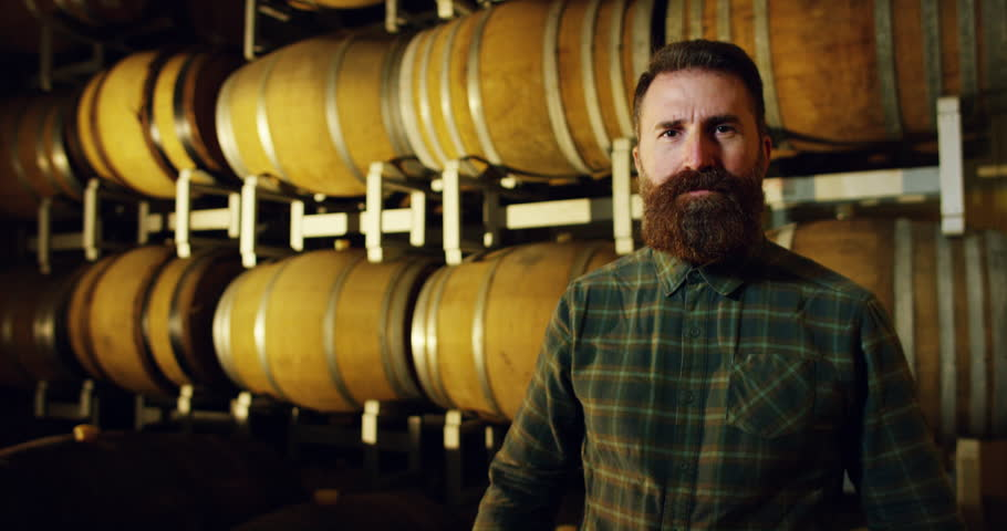 A brewmaster expert checks the quality of the freshly tapped beer from wooden barrels formerly used for flavour the wine or beer. passion for beer and wine. old and traditional jobs. | Shutterstock HD Video #21399307