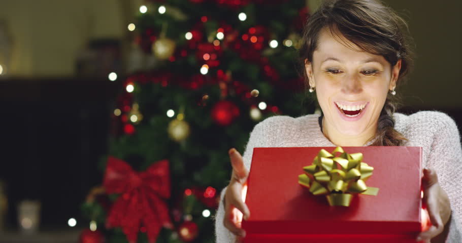 Girl with Christmas hat makes wishes and opens a Christmas gift package. concept of holidays and new year. the girl is happy and smiles with christmas gift in hand. | Shutterstock HD Video #21399445