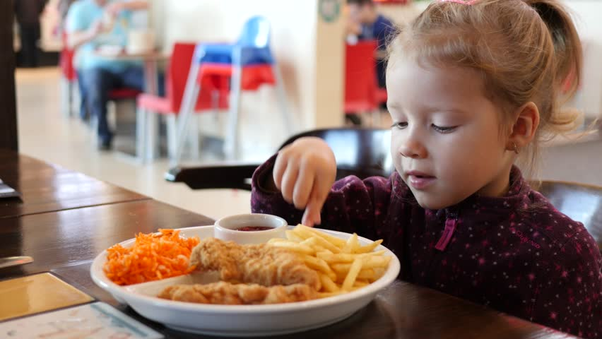 cute little kid girl portrait funny eating french fries in fast food court in a mall