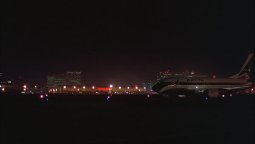 Night Pan Right Over Delta Commercial Airplane Waiting Tarmac Runway Take Off 2nd Plane