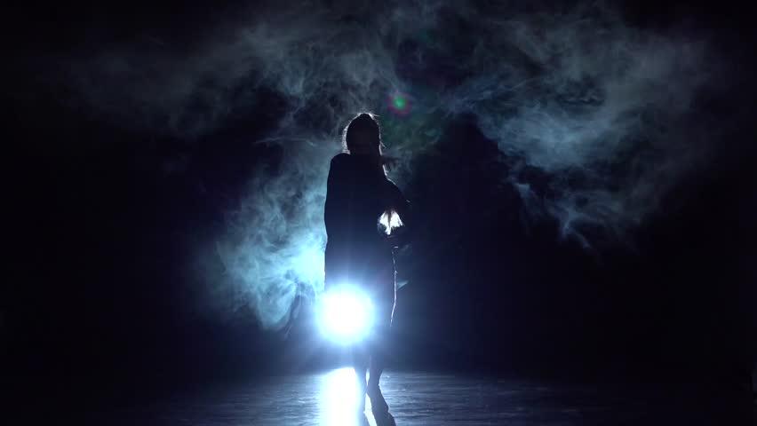 Girl dancing cha-cha-cha dance in the studio, silhouette. Slow motion