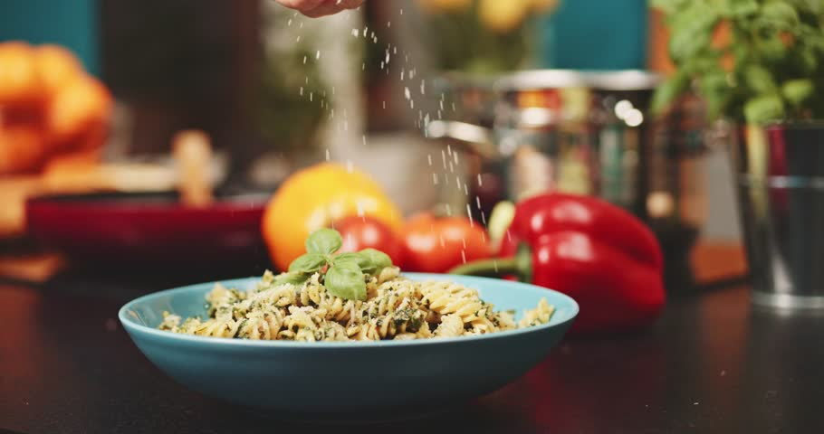 Putting parmesan cheese on pasta slow motion dolly shot woman hands covering fusilli pasta with italian cheese at the kitchen background delicious food home cooking healthy eating | Shutterstock HD Video #21469375