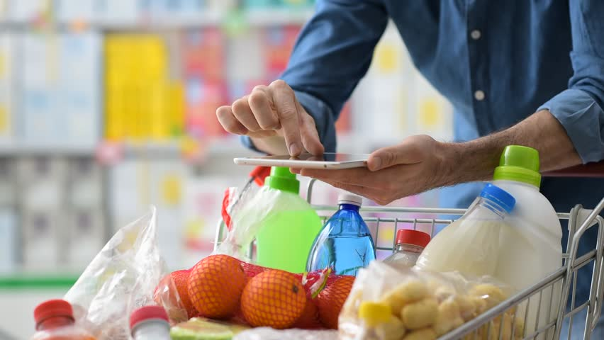 Man doing grocery shopping at the supermarket, he is leaning on a full shopping cart and using a digital tablet | Shutterstock HD Video #21481405