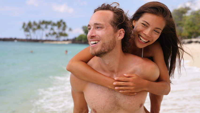 Attractive happy couple laughing having fun piggybacking on tropical beach. Caucasian man carrying Asian girlfriend having fun laughing on travel vacation. Healthy happy interracial people. Beach life