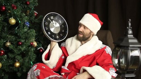 Bad Brutal Santa Claus Smiling And Shows The Clock Five Minutes To Twelve On The Background Of Christmas Tree