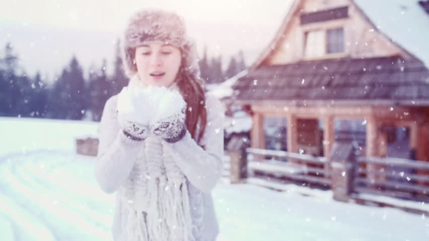 Blowing Snow, SLOW MOTION 120fps 4K DCi. Beautiful Joyful Female Model having fun near wooden log Cottage. Young woman enjoying magical snowfall. Winter wonderland. Snow Day near Mountain Chalet Cabin