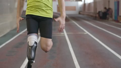 Slow motion shot of Paralympic athlete running on track. Animated hologram indicating his heart rate data