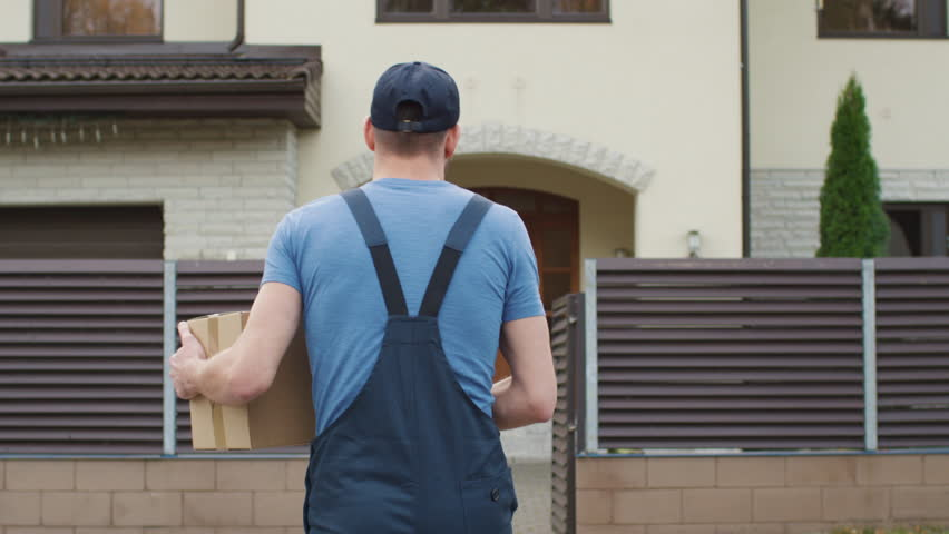 Delivery Man Comes To the Suburban House Door and Knocks. Camera Follows Him from the Back. Shot on RED Cinema Camera in 4K (UHD).