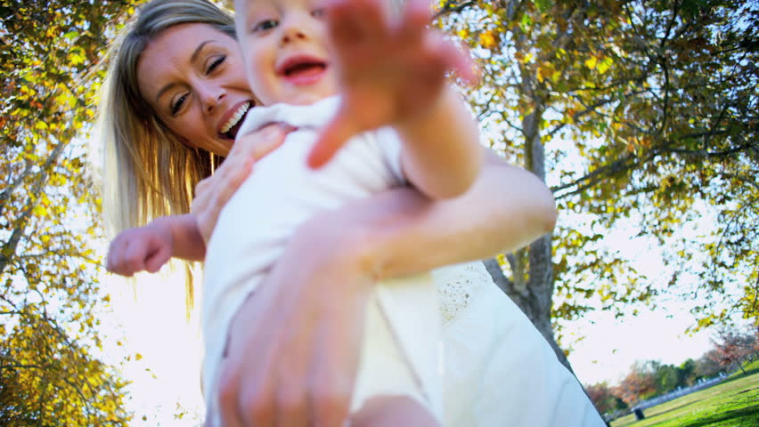 Blonde baby laughing as his beautiful young mom swings him through the air | Shutterstock HD Video #2153696