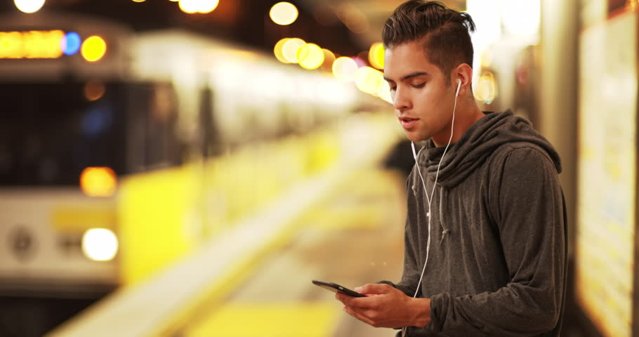 Millennial Latino man using smartphone waiting for subway train at metro station. Hispanic commuter using cell phone to listen to music at rail stop. 4k