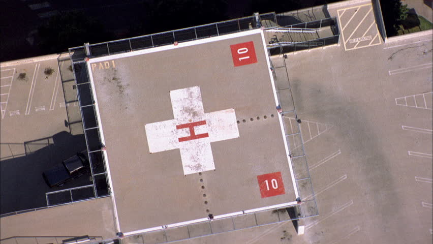 day Aerial Down angle red blue medevac helicopter hovers over helipad multi story ND building really hospital Pan right follow helicopter flies away over industrial area