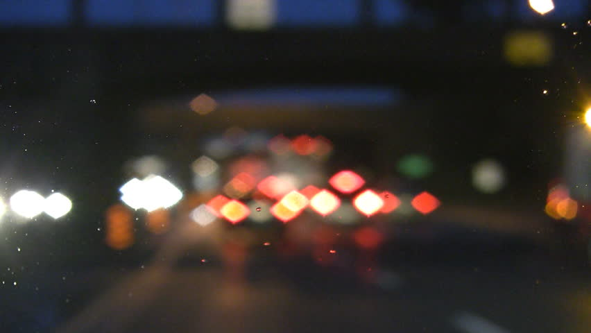 Defocused lights. Rainy highway drive. Emergency lights pass by and traffic slows.