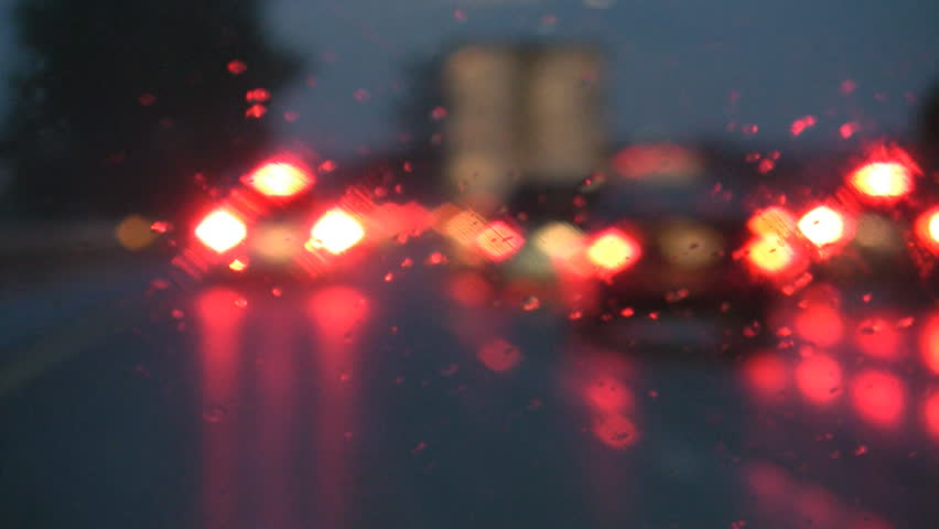 Defocused lights. Driving on a rainy highway, cars braking. Rain on windshield.
