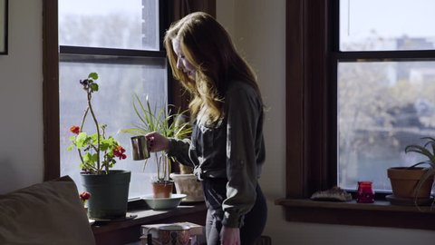 Young Woman Waters Her Plants In Her Trendy City Apartment