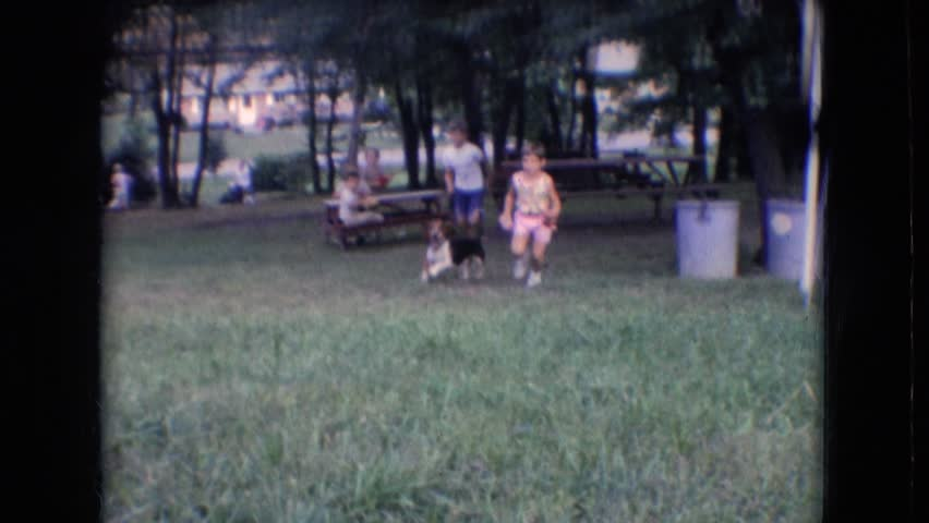 ATHENS OHIO 1966: children playing with basset hound in the yard.