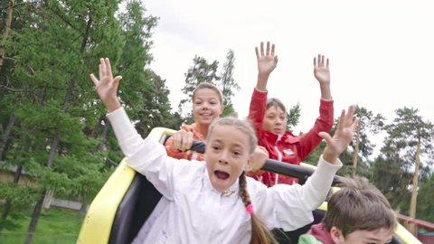 Group of exhilarated children shouting and raising arms while riding roller coaster. Shot made with action camera