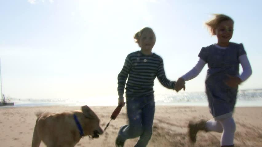 WIDE SHOT, Handheld, Children running hand in hand on beach with dog