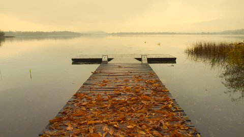 Wooden pier with leaves on the quiet lake at sunrise in autumn