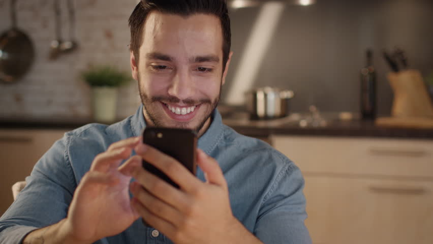 Handsome Young Man Smilingly Uses Smartphone in the Kitchen. Shot on RED Cinema Camera in 4K (UHD). | Shutterstock HD Video #21727765