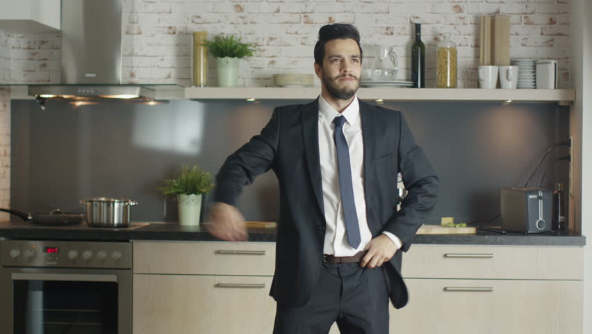 Classy and Handsome Young Businessman Dances Energetically at His Kitchen. Shot on RED Cinema Camera in 4K (UHD).