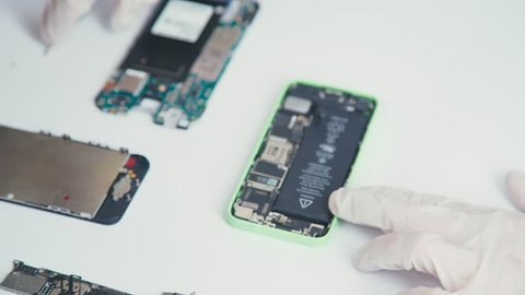 Close-up of a cell phone repair. The internal components of a smartphone. Disassembled cell phone. Cell Phone Battery. Master disassembled mobile device for detail. Chips and details of the smartphone