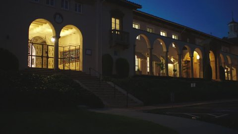 Dusk magic hour pan left 4 female students up steps into main entrance Spanish Style stucco high school catholic school tiled roof, arches religious emblem then pan right classrooms, see cross palm t