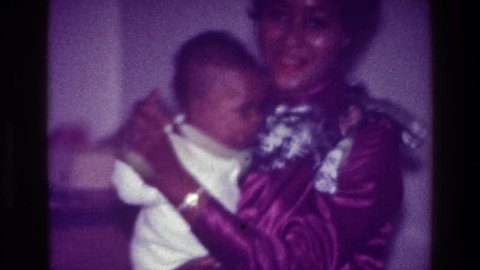 HARLEM NEW YORK 1976: mother carrying her child in hand, mom dancing with some food