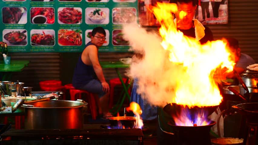 BANGKOK - NOV 18: A chef cooks food at a street-side restaurant in Chinatown on November 18, 2016 in Bangkok, Thailand.