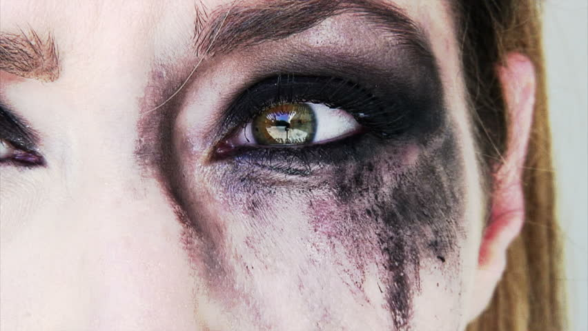 close up of a scared and crying woman with smeared make up