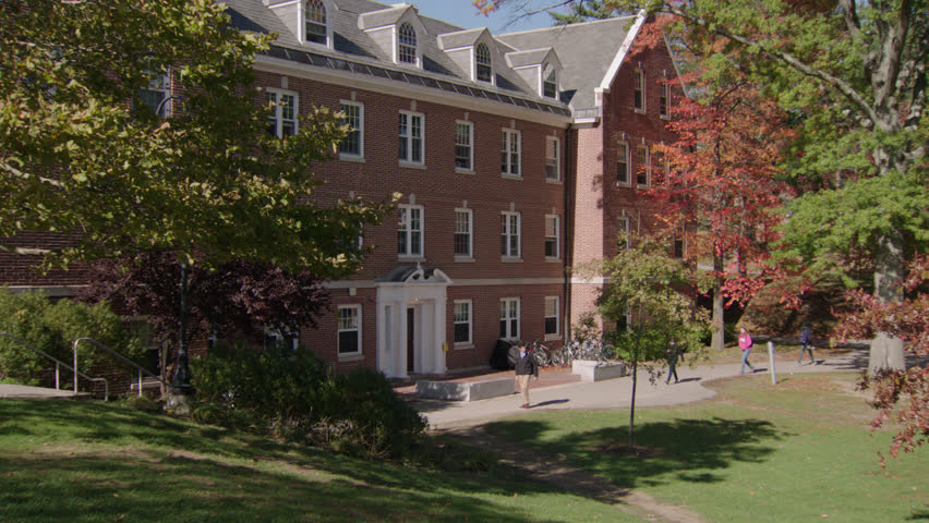 day eastern college campus then pans Left left 4 story brick school building dorm small entry columns, fancy dormers, bikes right, few students, fall autumn, (Oct 2012)