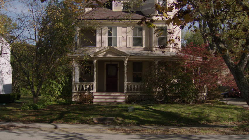 Day then pushes upstairs windows front beige wood clapboard house , wrap around porch, turret, bay windows, screened red door, autumn, fall trees (Oct 2012)