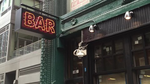New York City Daytime DX Establishing Shot of a Bar Pub. Day exterior video footage of a vintage neon sign. New York people go out in day to have fun, drink alcohol. Security camera in shot.