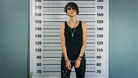 Female hacker catched in handcuffs in front of mugshot board