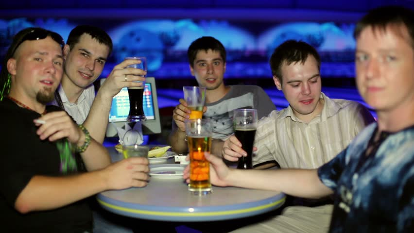 Five friends sit and drink bear in dark bowling club