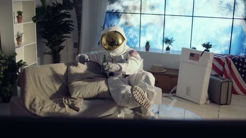 4K Astronaut relaxing in apartment, watching TV and drinking a beer (UK-Oct 2016)