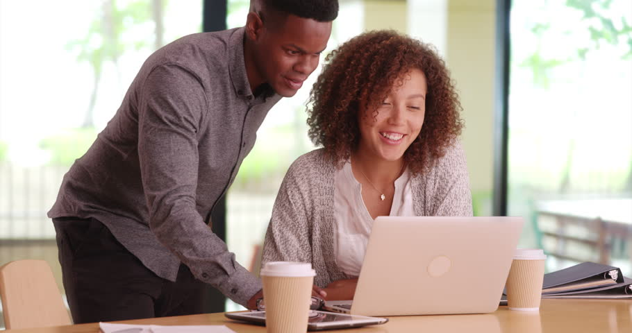 Young happy co-workers using a computer. African American workers at a start-up. Small business professionals at coffee shop. Black millennials at a startup browsing the internet. 4k. | Shutterstock HD Video #21850735
