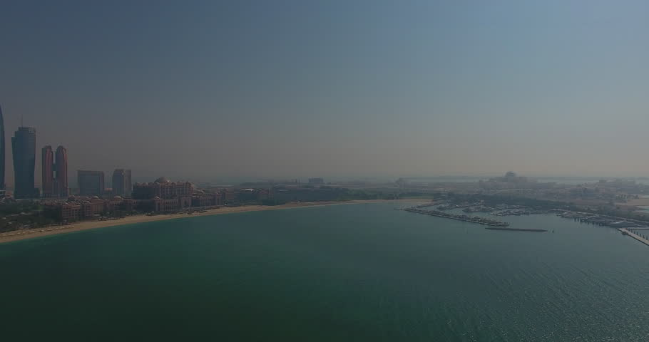 Panning past Emirates Palace over the water from above