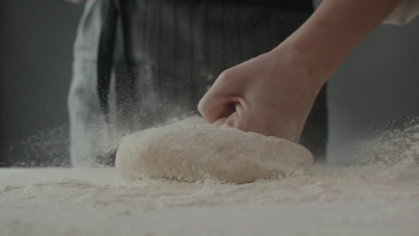 Baker kneading dough in flour on table, slow motion