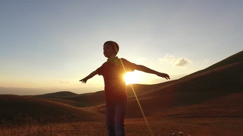 Kid silouette spreading arms and looking to the infinite at the sunset. Conceptual footage.