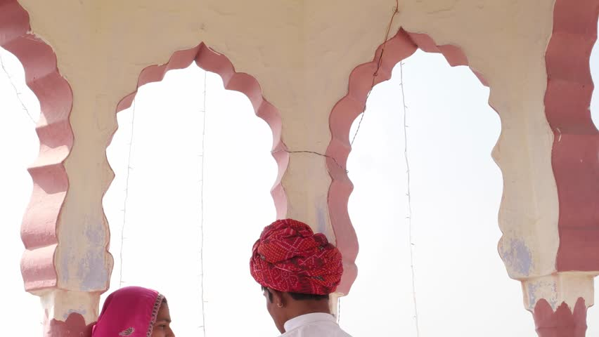 Tilt down to dating girl and boy under a rooftop canopy chattri talking in Rajasthan, India in pink sari and red turban and white kurta
