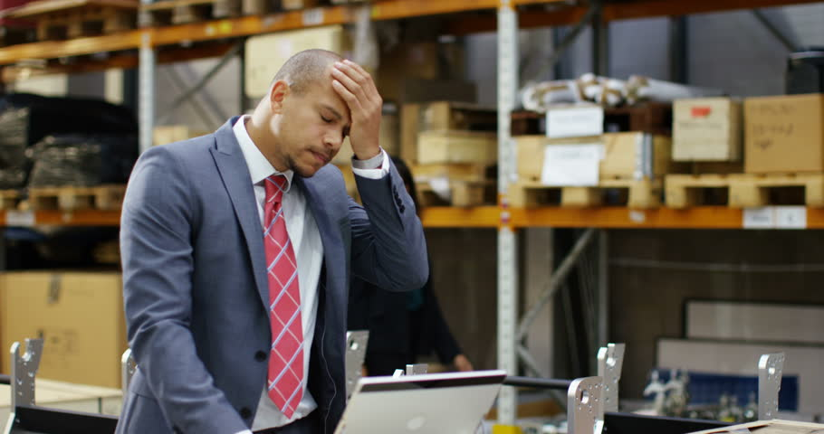 4k, Tired businessman with a concerned look working at a large warehouse. In slow motion.