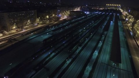 4K aerial shot of a trainstation during night, in winter