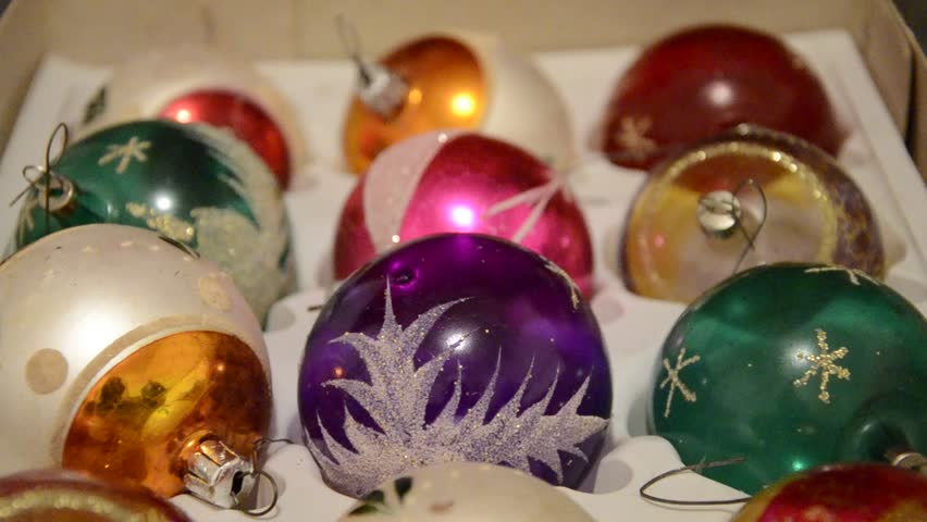 Close up of hand taking out shiny aged Christmas speheres from box. Detail of Man takes out vintage brightly XMas balls for decorating Christmas tree. Open box full of baubles in different colours