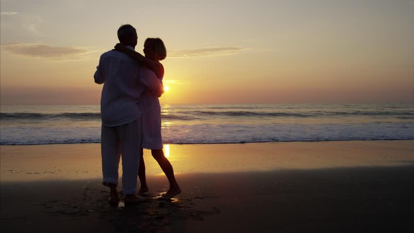 Silhouette loving Caucasian seniors retired healthcare relaxation freedom dance Summer holiday beach sunset dusk RED DRAGON   Shutterstock HD Video #22096735