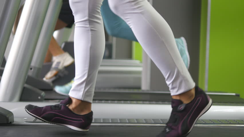 female legs walking and running on treadmill in gym young woman exercising during cardio workout