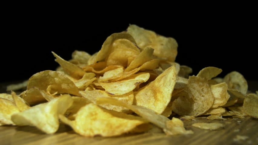 Potato Chips Rotating On Black Background. Potato chips are rotated on a black background. Close-up of yellow delicious chips randomly lying on a table. Excellent Footage for themes: Harmful food | Shutterstock HD Video #22145470